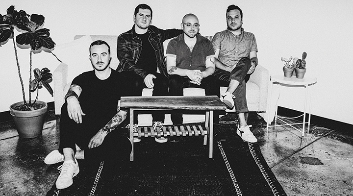 Band sitting on couch in black and white