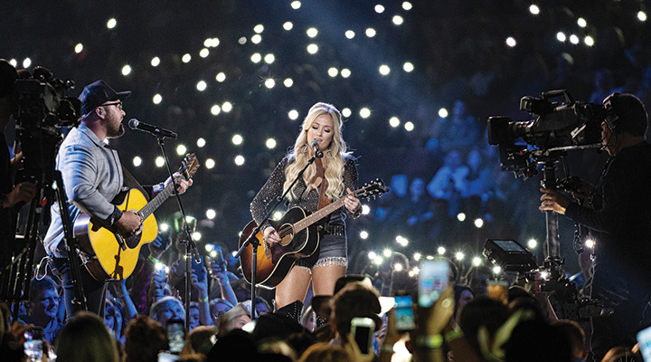 Musicians singing and playing guitar at Country Music Week